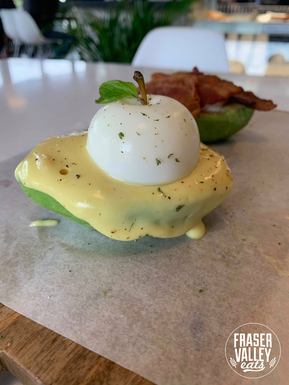 Avo Addict menu item, an egg in the shape of an apple and topped with a real apple stem sitting in an avocado half-shell covered in hollandaise sauce with a cream cheese-filled and bacon-covered avocado half in the background