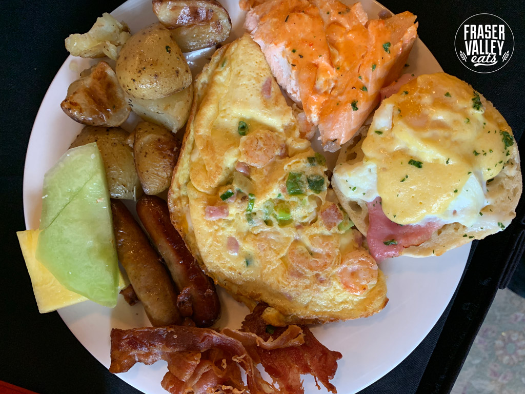 Omelette, eggs benedict, salmon, roast potatoes, bacon and sausage with melon and pineapple on a plate