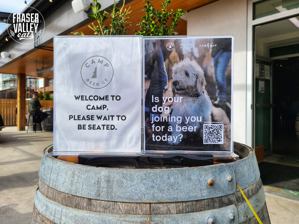 """Camp Beer Co welcome sign next to a photo of a dog that reads, """"Is your dog joining you for a beer today?"""""""