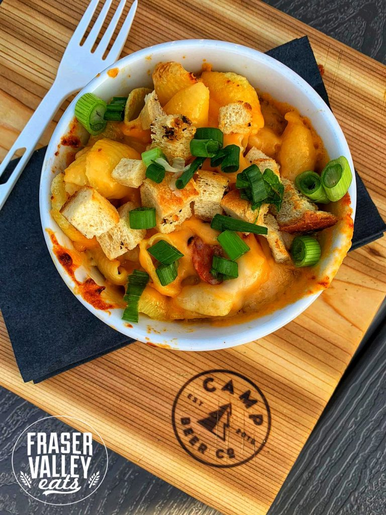 A bowl of cheesy pasta with sausage and croutons topped with green onions on a wooden board emblazoned with the Camp Beer Co logo.
