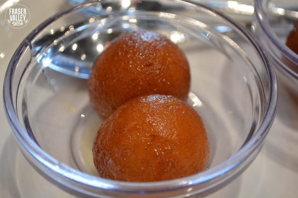 Two gulab jamun balls in a glass dish