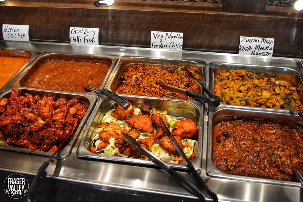 7 dishes in warming trays at An Indian Affair's lunch buffet with Tandoori Chicken front and center