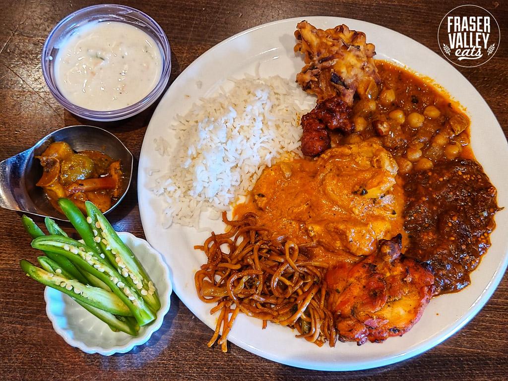 Veggie noodles, rice, tandoori chicken, butter chicken, channa masala, an onion  bhaji, khatte meethe baingan, and sides of raita, achar, and jalapenos