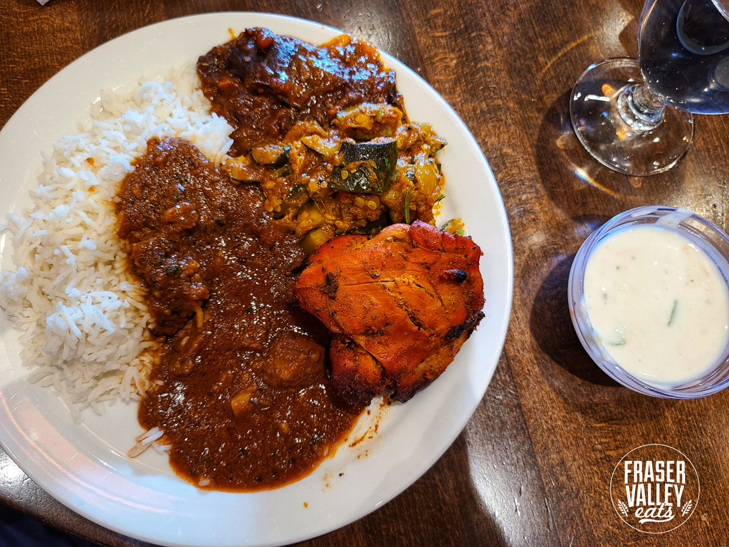 Rice with goat curry, tandoori chicken, zucchini masala, khatte meethe baingan, a side of raita, and water in a wine glass